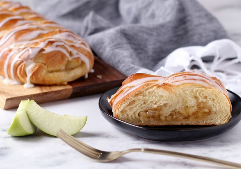 Apple Butter Braid Pastry with slice on plate, covered in icing, green apple slices next top late and fork. Has gray towel in background all on marble table